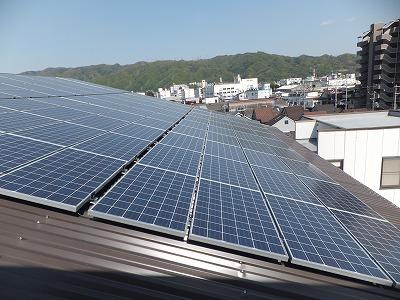 茶色の折板屋根の上に、太陽光パネルを設置